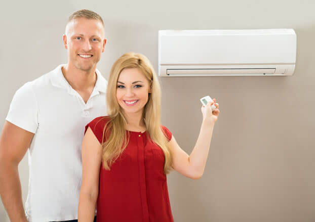 man and woman demonstrating ductless ac with remote