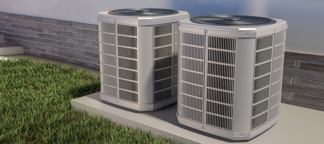 two side by side heat pumps outside building
