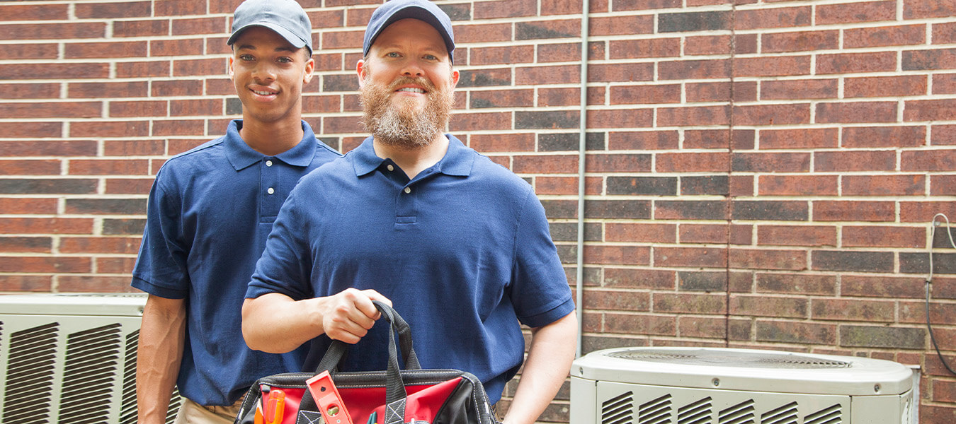 two smiling hvac techs carrying tools